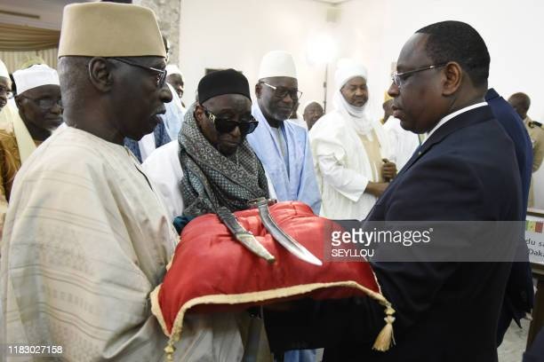 Senegal President Macky Sall receives the sword El Hadj Omar Saidou Tall during a ceremony with French Prime Minister Edouard Philippe at the Palace...