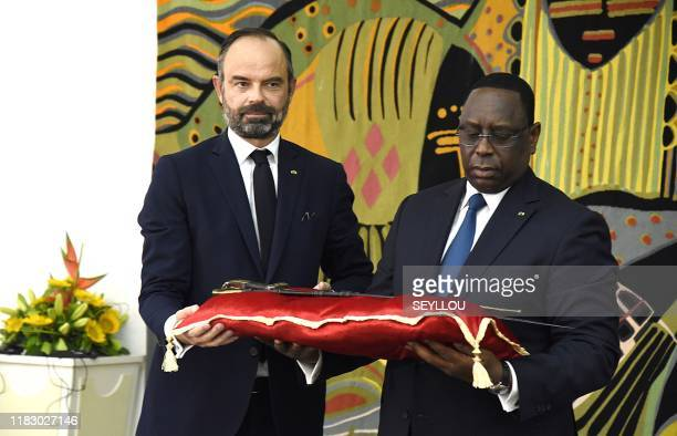 Senegal President Macky Sall receives the sword El Hadj Omar Tall from French Prime Minister Edouard Philippe at the Palace of the Republic in Dakar,...