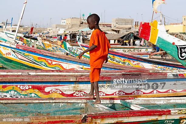 Senegal, Saint Louis, boy (10-11) standing on rowboat