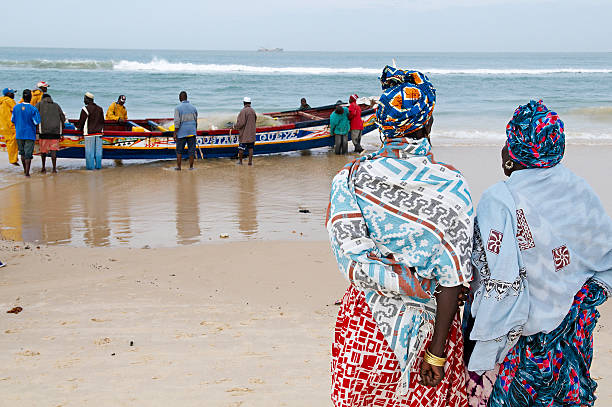 Senegal, Saint Louis, people on beach with rowboat, two women in foreground