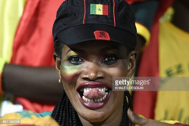 Senegal supporter sticks her tongue out during the 2017 Africa Cup of Nations group B football match between Tunisia and Senegal in Franceville on...