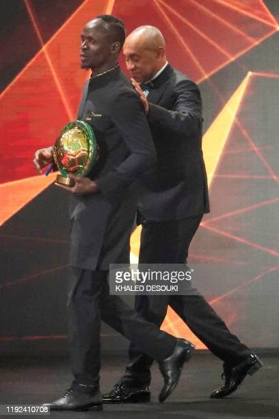 Senegal winger Sadio Mane carries the Player of the Year award as he is escorted off stage by Ahmad Ahmad President of the Confederation of African...