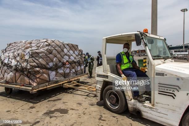 Senegales authorities and airport staff unload cargo sent from Alibaba cofounder Jack Ma after it arrives at at the DakarBlaise Diagne Airport in...