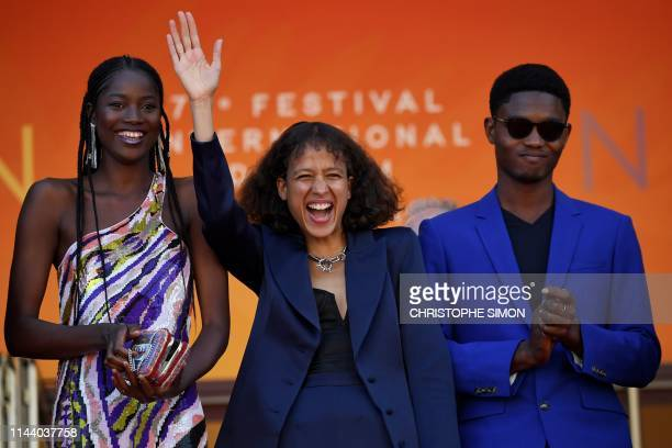 Senegalese actress Mama Sane French actress and film director Mati Diop and Senegalese actor Ibrahima Traore pose as they arrive for the screening of...