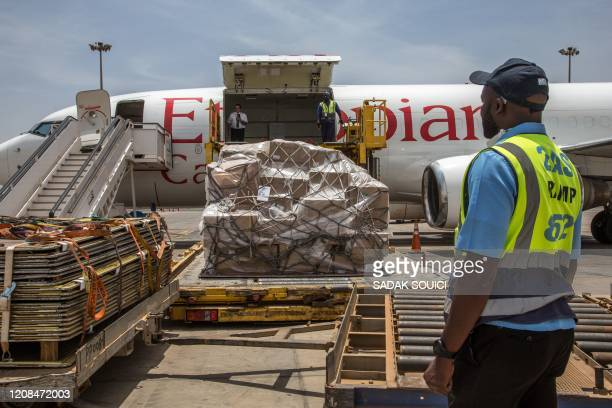 Senegalese authorities and airport staff unload cargo sent from Alibaba cofounder Jack Ma after it arrives at at the DakarBlaise Diagne Airport in...