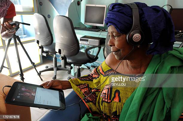 Senegalese Boury Guisse uses a tablet computer in the world's first cybercafe equipped with tablet computers in the Medina popular district of Dakar...