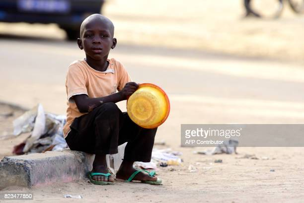 A Senegalese child sits in a street of Guediawaye near Dakar while begging for money or food on July 19 2017 Senegal's talibes children as young as...