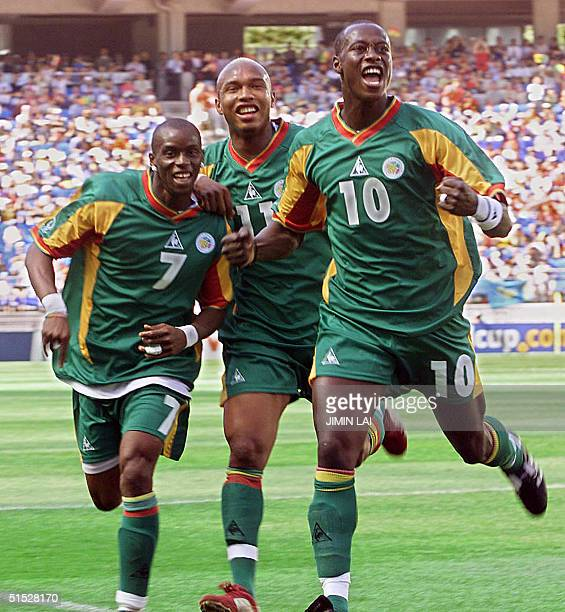 Senegalese defender Khalilou Fadiga celebrates his goal from a penalty kick with teammates Henri Camara and El Hadj Diouf in their Group A match...