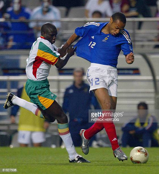 Senegalese defender Omar Daf grabs French forward Thierry Henry during their 2002 FIFA World Cup Korea/Japan opening match in Seoul 31 May 2002...