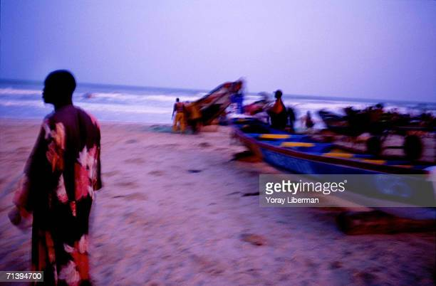 A Senegalese fisherman stands on the beach and watches fishing boats sail away April 16 2003 in the village of Mboro Senegal The firemen from the...