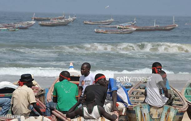 Senegalese fishermen and boat owners wear red headbands in sign of protest as they sit on the beach on March 30 2011 in Kayar 52 kms northwest of...