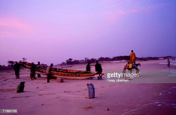 Senegalese fishermen push their fish boats into the water on the beach April 16 2003 in the village of Mboro Senegal The firemen from the village...