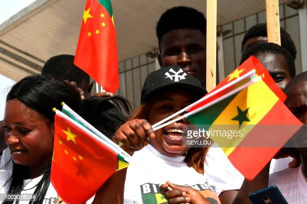Senegalese hold Chinese and Senegalese flags upon the arrival of Chinese President Xi Jinping for a state visit on July 21, 2018 in Dakar.
