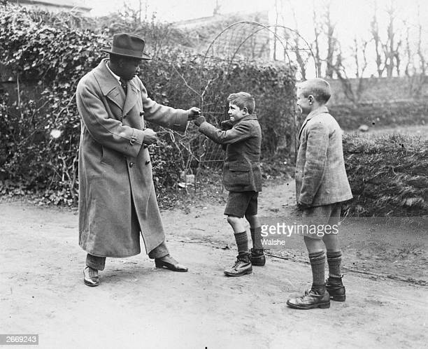 Senegalese light-heavyweight world champion boxer Battlin' Siki mock-boxing with two boys in Dublin.