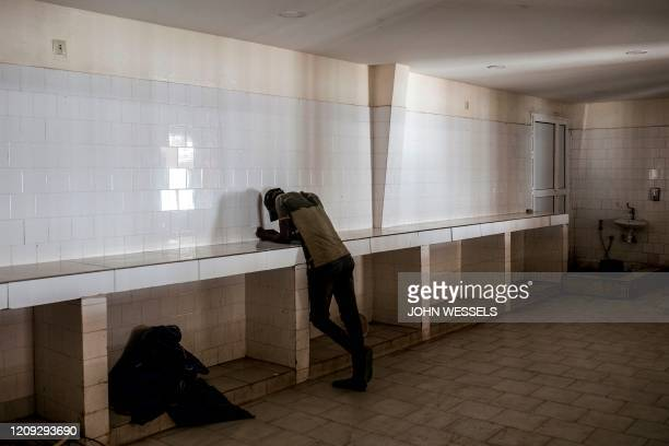 Senegalese man is seen in an empty room at the export side of the Hann - Bel Air fishing docks in Dakar on April 3, 2020. - Usually bustling with...