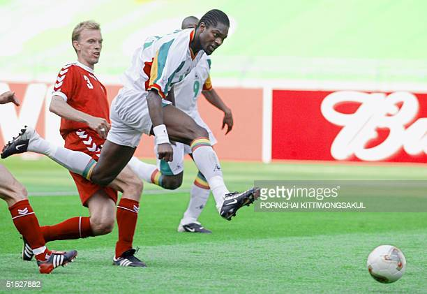 Senegalese midfielder Salif Diao scores against Denmark as Danish defender Rene Henriksen looks on in their Group A match at the 2002 FIFA World Cup...
