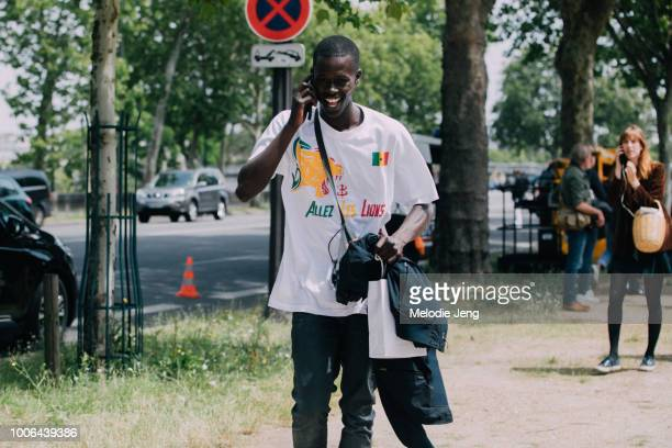 Senegalese model Alpha Dia talks on the phone and wears an Allez Les Lions Senegal football shirt after the Balmain show during Paris Fashion Week...