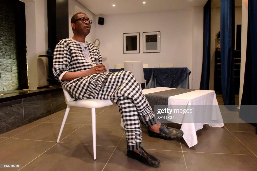 Senegalese musician Youssou N'Dour speaks during an interview on March 13, 2017 at a restaurant in Dakar. /