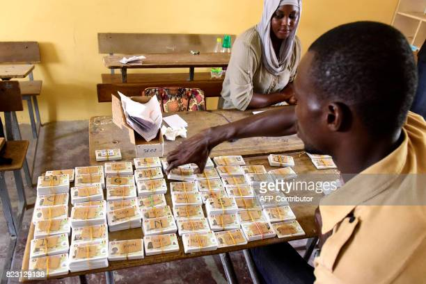 TOPSHOT Senegalese officials sort out voter ID cards in alphabetical order at a school that will be used as a polling station in Dakar on July 26...