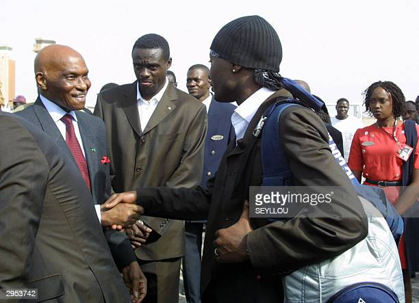 Senegalese President Abdoulaye Wade greets Senegal player Lamine Sakho while captain Pape Malicke Diop looks on after their arrival at Dakar Airport...
