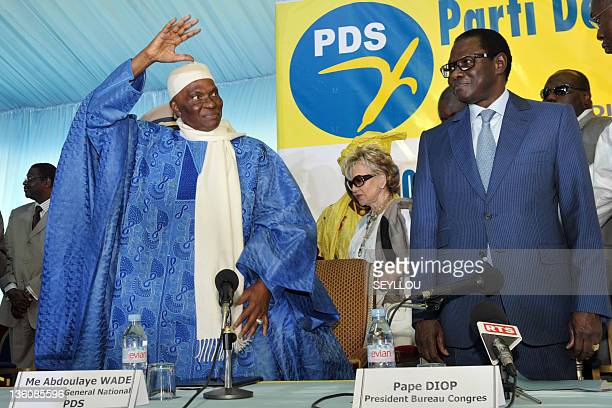 Senegalese President Abdoulaye Wade salutes the crowd next to Pape Diop president of the Senate at a hotel in Dakar on December 23 2011 during a...
