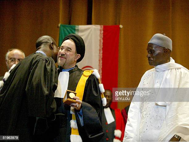 Senegalese President Abdoulaye Wade watches Iranian President Mohammad Khatami as he is awarded an honorary doctor's degree by Abdu Salam Sall rector...