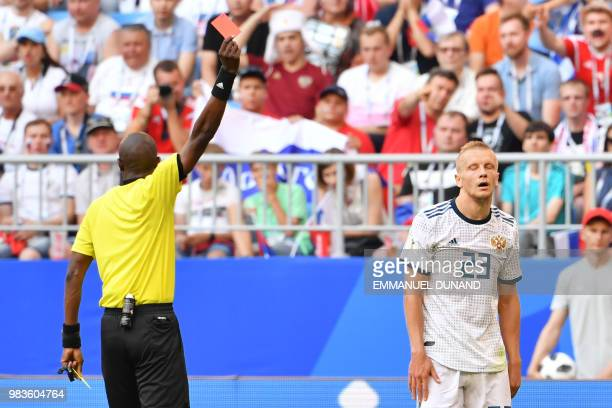 Senegalese referee Malang Diedhiou shows a red card to Russia's defender Igor Smolnikov during the Russia 2018 World Cup Group A football match...