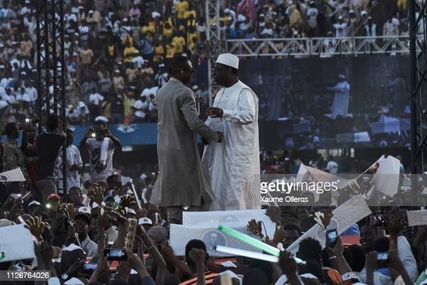 Senegalese singer Youssou N'Dour greets president Macky Sall at Leopold Sedar Senghor stadium during his final rally on February 22 in Dakar Senegal...