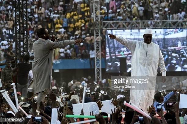 Senegalese singer Youssou N'Dour greets president Macky Sall at Leopold Sedar Senghor stadium during his final rally on February 22 in Dakar Senegal...