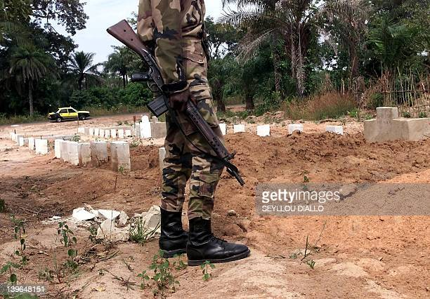 Senegalese soldier stands in a cemetary where are buried the victims of the sinking of Joola in the village of Kantene 26 November 2002