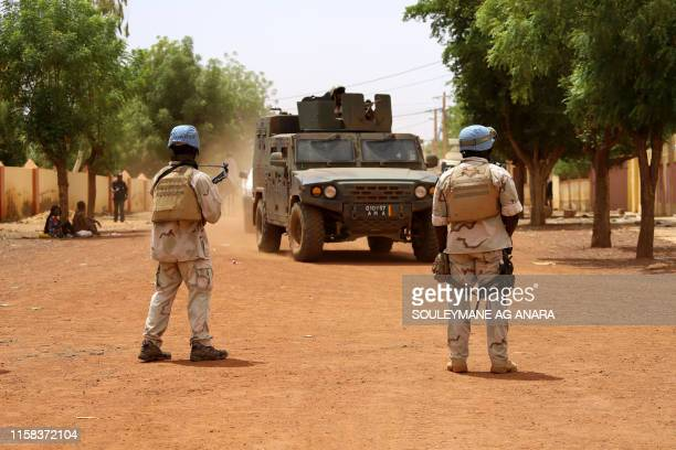Senegalese soldiers of the UN peacekeeping mission in Mali MINUSMA patrol in the streets of Gao on July 24 as an armoured vehicle of the FAMA drives...