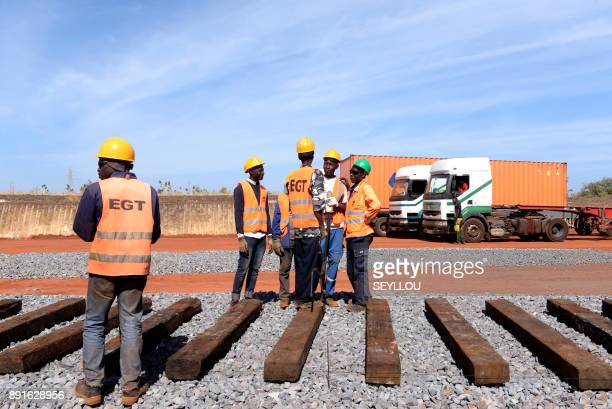 Senegalese workers manouver sleepers as they construct a section of track of the Regional Express Train on the outskirts of Dakar on December 13 2017...