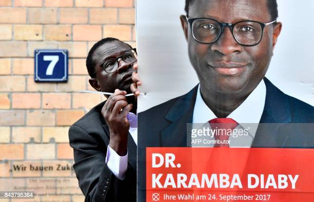 Senegaleseborn German MP for the Social Democratic Party Karamba Diaby puts up a campaign poster in Halle on September 6 2017 Diaby will be defending...