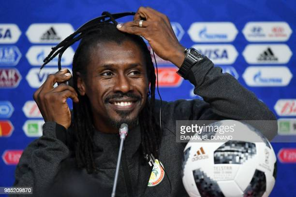Senegal's coach Aliou Cisse adjustes his headphones during a press conference on the eve of the Russia 2018 World Cup Group H football match between...