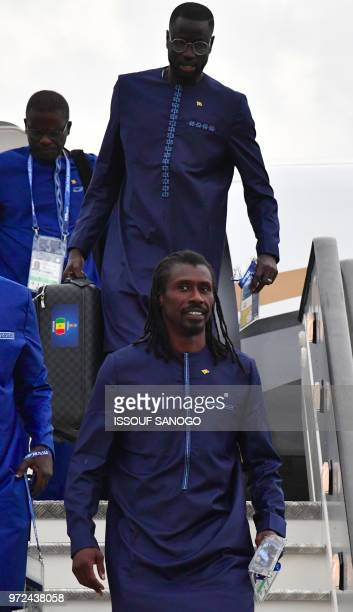 Senegal's coach Aliou Cisse and Senegal's midfielder Cheikhou Kouyate as they disembark from a plane upon the team's arrival in Kaluga on June 12...