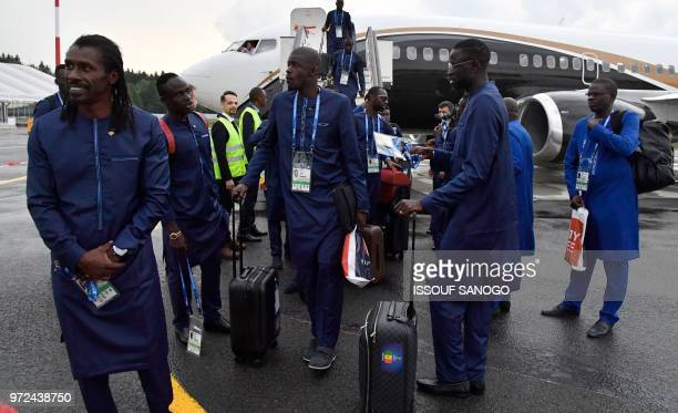 Senegal's coach Aliou Cisse and Senegal's midfielder Cheikhou Kouyate disembark from a plane upon the team's arrival in Kaluga on June 12 ahead of...