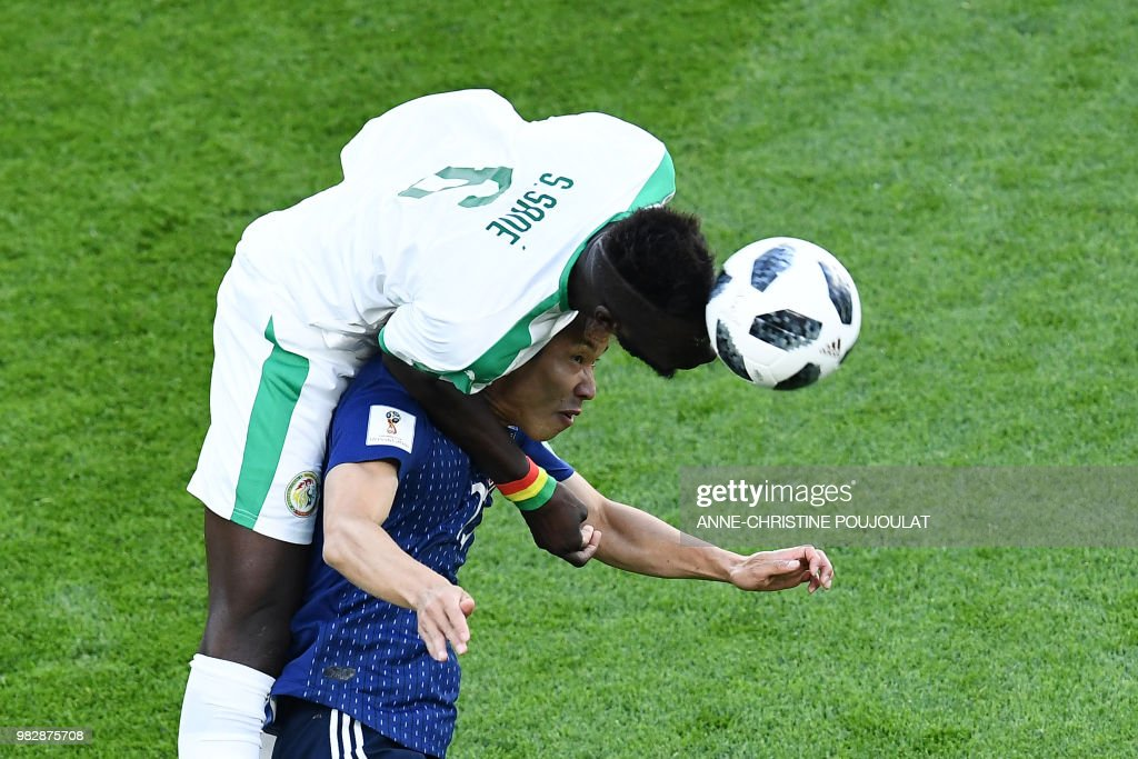 TOPSHOT - Senegal's defender Salif Sane (top) vies with Japan's forward Yuya Osako during the Russia 2018 World Cup Group H football match between Japan and Senegal at the Ekaterinburg Arena in Ekaterinburg on June 24, 2018. (Photo by Anne-Christine POUJOULAT / AFP) / RESTRICTED