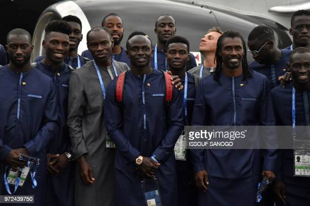 Senegal's forward Sadio Mane and Senegal's coach Aliou Cisse pose with teammates upon the team's arrival in Kaluga on June 12 ahead of the Russia...