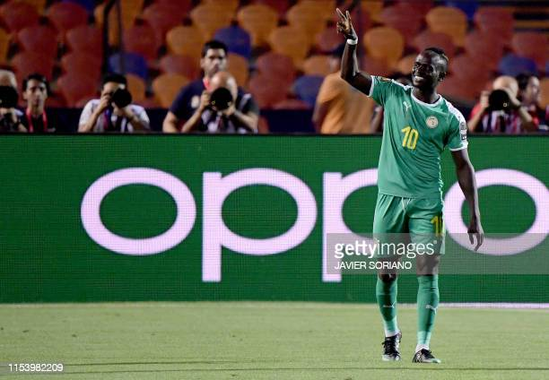 Senegal's forward Sadio Mane flashes the victory gesture as he reacts after scoring a goal during the 2019 Africa Cup of Nations Round of 16 football...