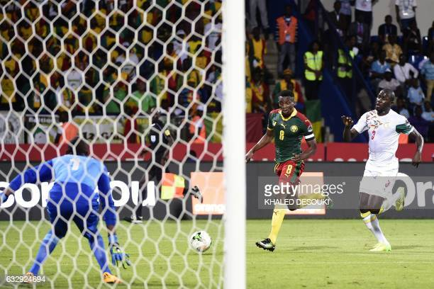 Senegal's goalkeeper Abdoulaye Diallo prepares to block a shot on goal by Cameroon's forward Benjamin Moukandjo next to Senegal's defender Kalidou...