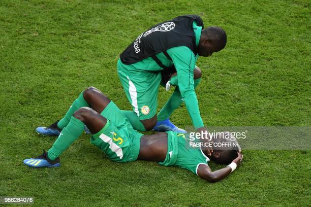 TOPSHOT Senegal's midfielder Idrissa Gana Gueye is comforted by a teammate at the end of the Russia 2018 World Cup Group H football match between...