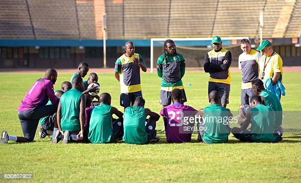 Senegal's national football team head coach Aliou Cisse coach advisor Omar Daf staff members and players take part in a training session on January 2...