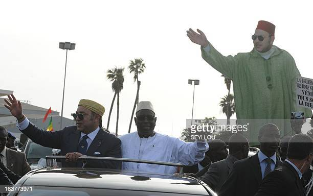 Senegal's President Macky Sall and Moroccan King Mohammed VI wave to people one of them holding a cardboard effigy of the King as they stand in a...