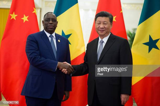 Senegal's President Macky Sall shake hands with China's President Xi Jinping before their bilateral meeting at the Great Hall of the People on...