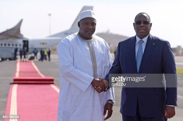 Senegal's President Macky Sall shakes hands with the new President of Gambia Adama Barrow prior to leaving the Senegalese capital Dakar for The...