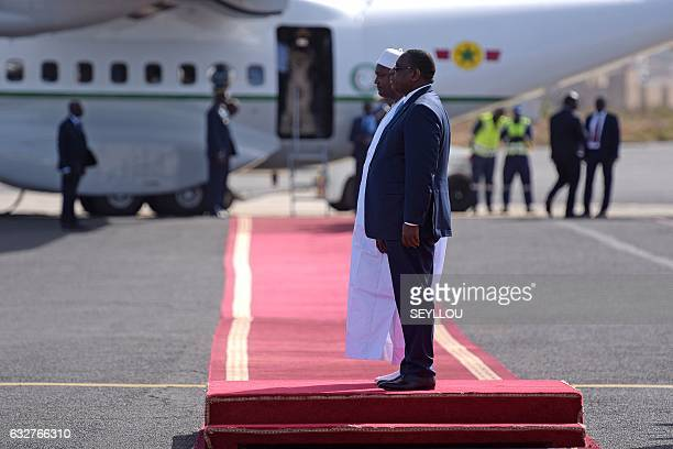 Senegal's President Macky Sall stands with the new President of Gambia Adama Barrow during a ceremony prior to leaving the Senegalese capital Dakar...
