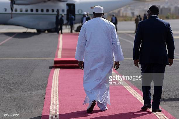 Senegal's President Macky Sall walks with the new President of Gambia Adama Barrow during a ceremony prior to leaving the Senegalese capital Dakar...