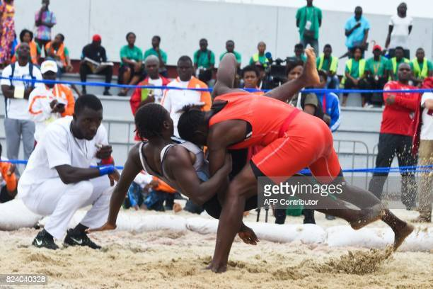 Senegal's Safietou Goudiaby puts down Guinea's Koumba Sow on July 28 2017 during the women folk wrestling semifinals at the Parc des Sports in...