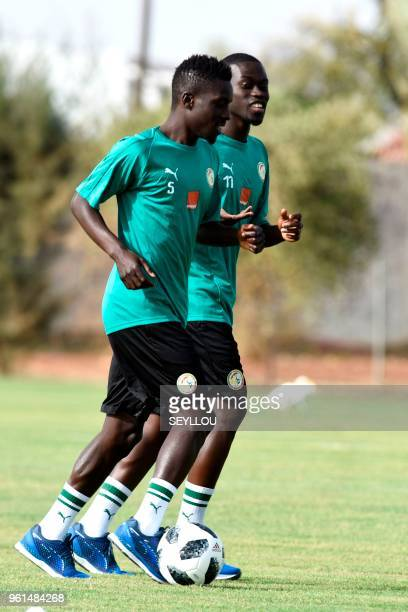 Sengalese footballers Idrissa Gana Gueye and his teammate Pape Alioune Ndiaye jog as they take part in a training session at The Diambars Training...
