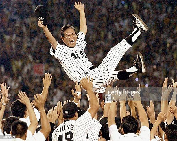Senichi Hoshino manager of Hanshin Tigers is tossed in the air by players after clinching their first league championship in 18 years at the Koshien...